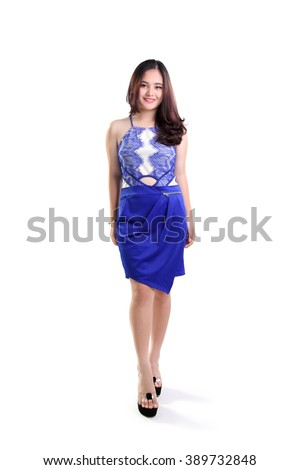 Beautiful smiling Asian female fashion model walking in a trendy blue dress, full length shot isolated on white background - stock photo