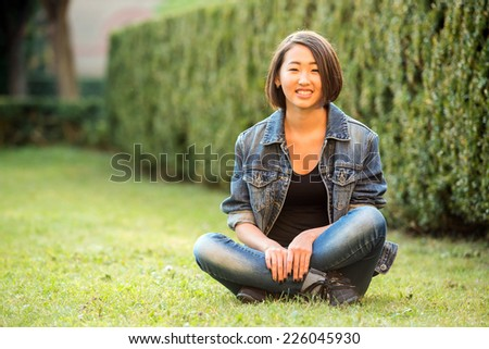 Beautiful smiling asian female student is sitting on the grass near the college. - stock photo