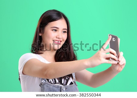 Beautiful smiling Asian teenage girl taking picture with her smartphone camera, on light green background - stock photo