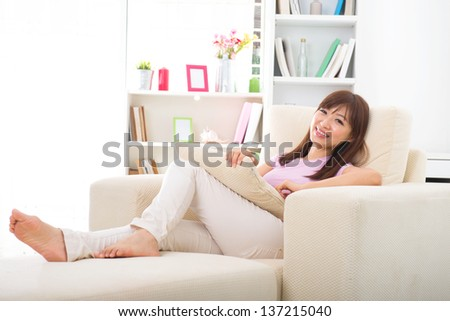 Beautiful smiling Asian woman with tablet computer. Lying on sofa  - stock photo