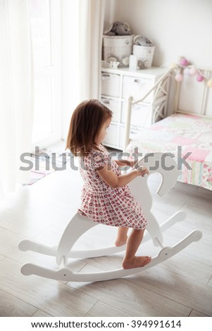 Beautiful smiling baby girl on a toy wooden horse. Brunette, toy, game - stock photo