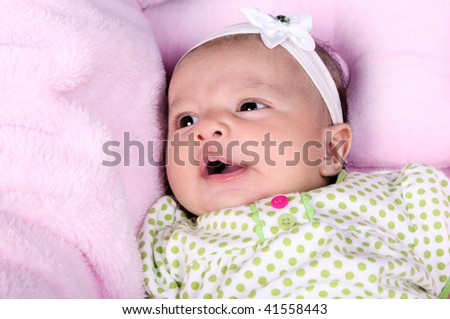 Beautiful smiling baby on a blanket pink - stock photo