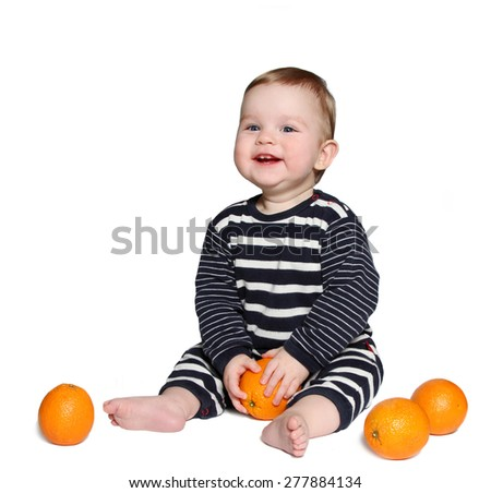 beautiful smiling baby sits with orange in hands on white background - stock photo