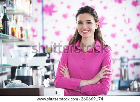 Beautiful smiling barista posing in a cafe, coffee machine on the background - stock photo
