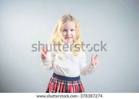 Beautiful smiling blond girl in a school uniform - stock photo