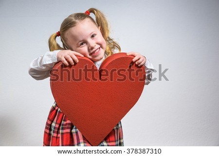 Beautiful smiling blond girl in a school uniform with a big red heart on Valentine's Day. - stock photo