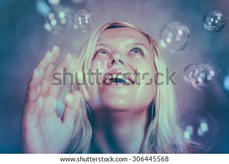 Beautiful smiling blond girl looking up and enjoying fabulous wonderland. - stock photo