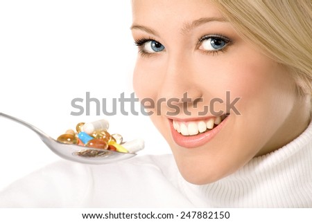 Beautiful smiling blond with blue eyes eating a lot of colorful pills on the spoon - stock photo