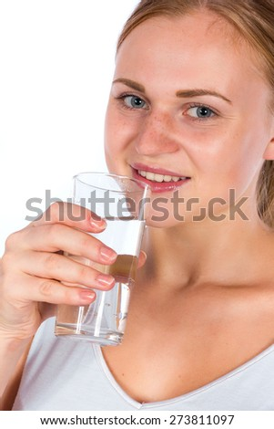 Beautiful smiling blonde girl holding a glass of water. A young athletic woman holding a transparent glass with water