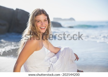 Beautiful smiling blonde in sundress sitting on the beach on a sunny day - stock photo