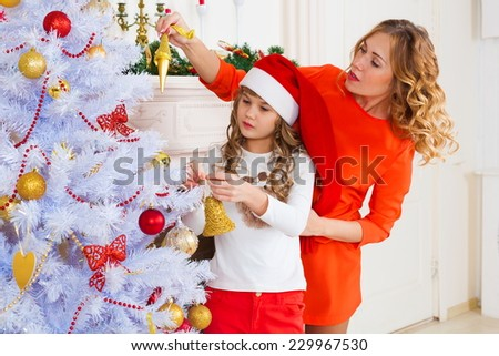 beautiful  smiling  blonde  mother and daughter near  the christmas tree with gifts have red clothes - stock photo