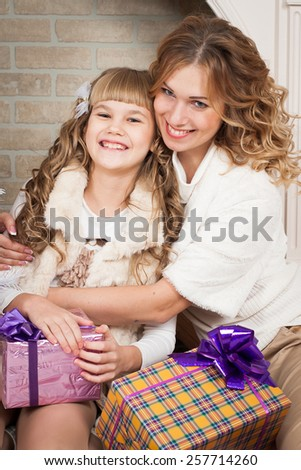 beautiful  smiling  blonde  mother and daughter tree with gifts, mother's Day, March 8 - stock photo