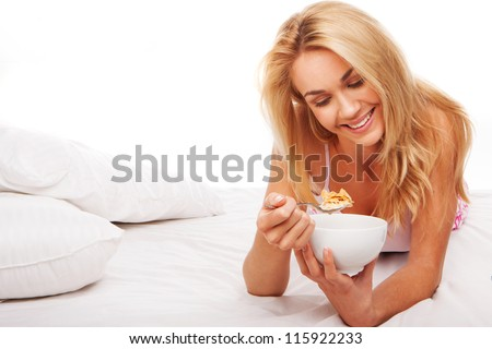 Beautiful smiling blonde woman eating a bowl of cereal lying on her stomach on her bed with copyspace