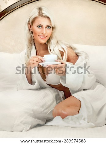 Beautiful smiling blonde woman with cup of coffee in bed