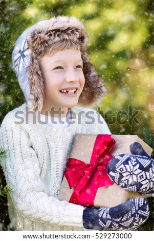 beautiful smiling boy in trapper hat, sweater and mittens holding nicely wrapped christmas gift by the tree or in the forest enjoying snowy cold winter weather, holiday or happiness concept