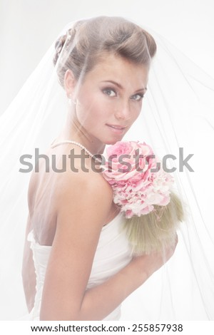 Beautiful smiling bride in the veil with bouquet at the gray background - stock photo