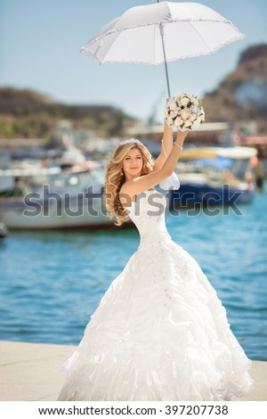 Beautiful smiling bride in wedding dress with white umbrella posing over seafront, outdoor bridal portrait. Happy fun young woman.  - stock photo