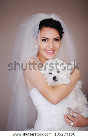 Beautiful Smiling Brunette Bride with small dog posing - stock photo