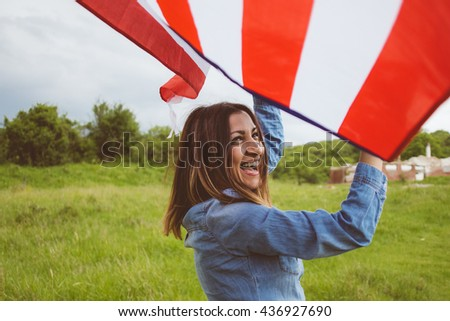 Beautiful smiling brunette girl running carefree over the green field, waving the American flag - stock photo