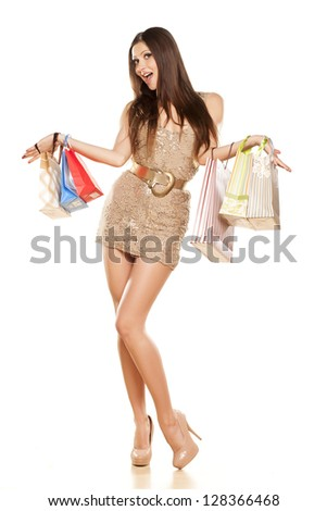 beautiful smiling brunette in a dress, holding a shopping bags in her hands on white background