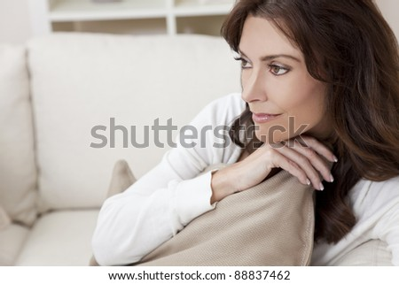 Beautiful smiling brunette woman at home sitting on sofa or settee holding a cushion and thinking - stock photo