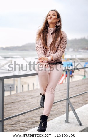 Beautiful smiling brunette woman sitting on a fence in front of town beach, smiling and looking at camera, fashion autumn outfit