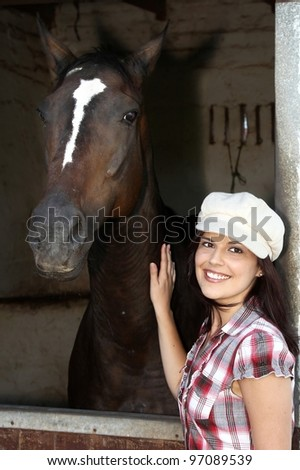 Beautiful smiling brunette woman with her horse in a stable