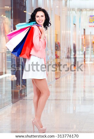 Beautiful smiling brunette woman with shopping bags in casual in the big mall - stock photo
