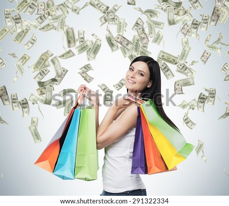 Beautiful smiling brunette woman with the colourful shopping bags from the fancy shops. Falling dollar notes from the ceiling. - stock photo