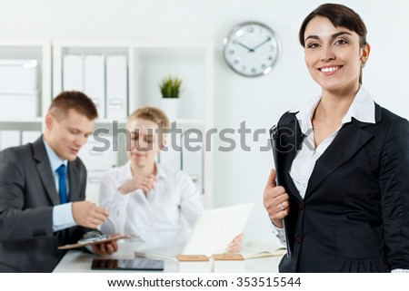 Beautiful smiling business woman in suit holding clipboard in hands while couple employees working in background. Serious business and partnership, conference, job offer, financial success concept - stock photo
