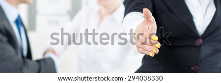 Beautiful smiling business woman in suit offering hand to shake while couple employees working in background. Serious business and partnership concept. Formal greeting and welcoming gesture - stock photo