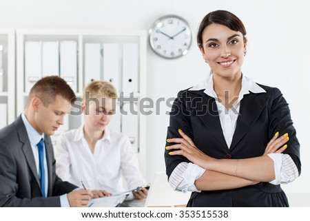 Beautiful smiling business woman in suit standing with hands crossed on chest while couple employees working in background. Serious business and partnership, job offer, financial success concept - stock photo