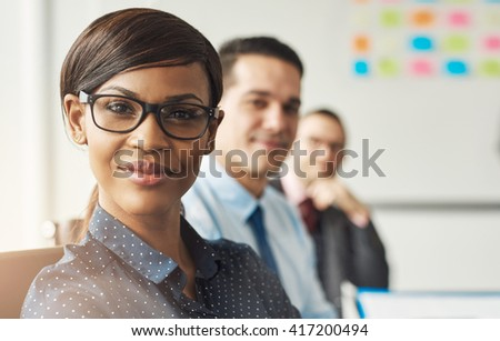 Beautiful smiling business woman wearing eyeglasses and white polka dotted shirt seated with male co-workers at work - stock photo