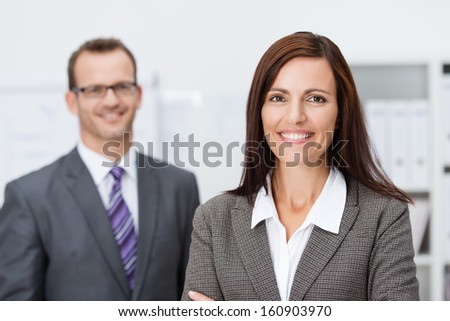 Beautiful smiling businesswoman standing with folded arms looking at the camera with a beaming friendly smile watched in the background by her male colleague - stock photo
