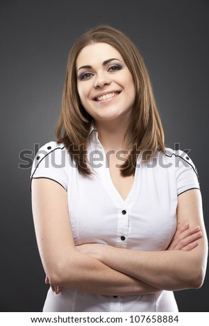 Beautiful smiling casual style portrait of woman in white, isolated on gray background - stock photo