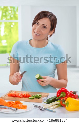 beautiful smiling caucasian model holding cucumber with kitchen knife and looking at camera - stock photo