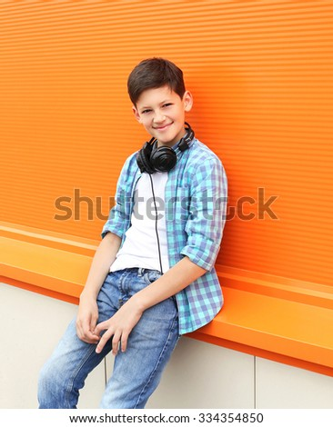 Beautiful smiling child boy wearing a shirt and headphones in city - stock photo