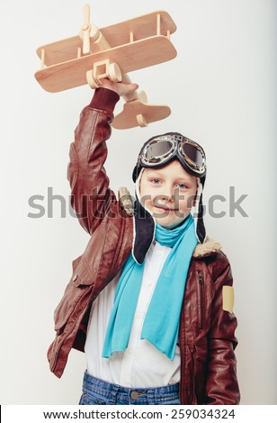 Beautiful smiling child (kid, boy) in helmet on a blue background playing with a plane. Vintage pilot (aviator) concept - stock photo