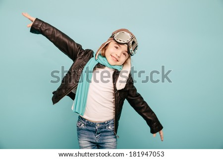 Beautiful smiling child (kid, girl) in helmet on a blue background playing with a plane. Vintage pilot (aviator) concept