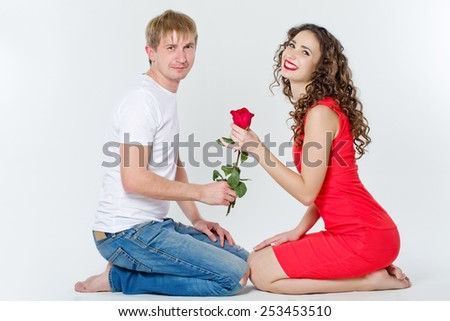 beautiful smiling couple with red rose on white background