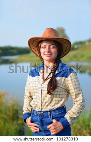 Beautiful Smiling Cowgirl front of lake - stock photo