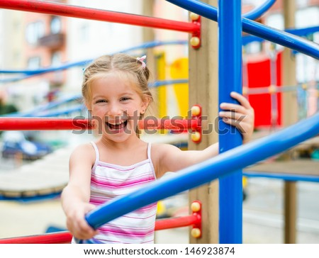 beautiful smiling cute girl on a playground - stock photo