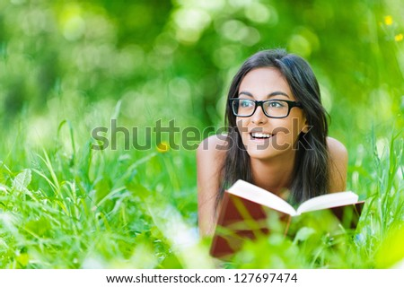 Beautiful smiling dark-haired young woman lying on grass and reading red book, against summer green park. - stock photo