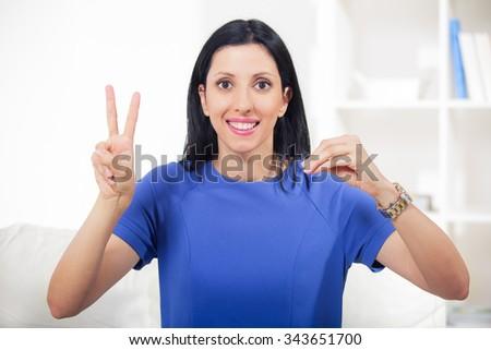 Beautiful smiling deaf woman using sign language - stock photo