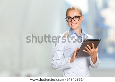 Beautiful smiling doctor woman in medical gown