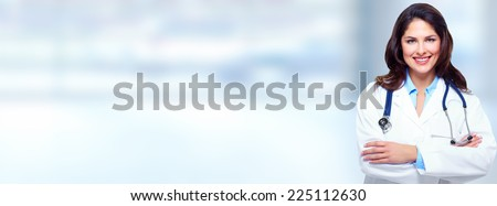 Beautiful smiling doctor woman over blue hospital background - stock photo