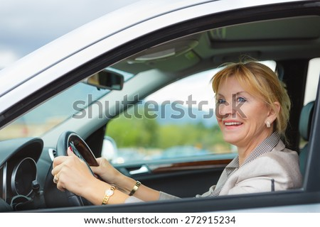 Beautiful smiling elderly woman 55-60 years with white teeth in suit at the whee, Driving a Car Through the mountains - stock photo