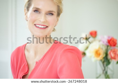 Beautiful smiling elegant woman indoors wearing pink blouse and short blond hair. - stock photo