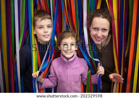 Beautiful smiling family of three against the multi-colored ribbon labyrinth, focus on the little girl. - stock photo