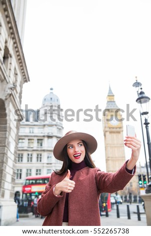 Beautiful smiling, fashion woman taking selfie on phone and showing thumb up
